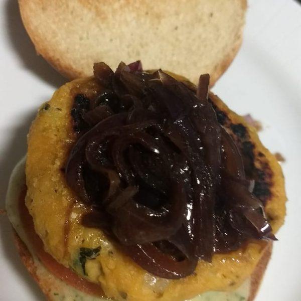 Hambúrguer de grão de bico com maionese de macaxeira com ervas e cebola roxa caramelizada com melaço de cana.